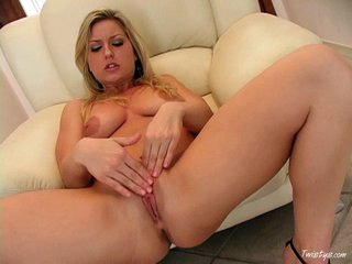 Solo babe Avy Scott massaging her love button and pussy with her fingers on the ottoman