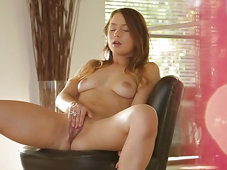 A brunette is doing solo self penetration on the chair